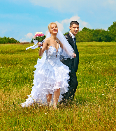 Couple wedding with flower  running outdoor. photo