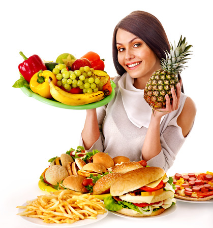 Happy woman choosing between fruit and hamburger. photo