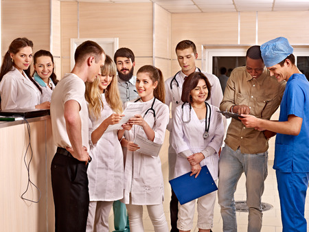 Group happy doctors standing at reception in hospital. Stock Photo - 27304895