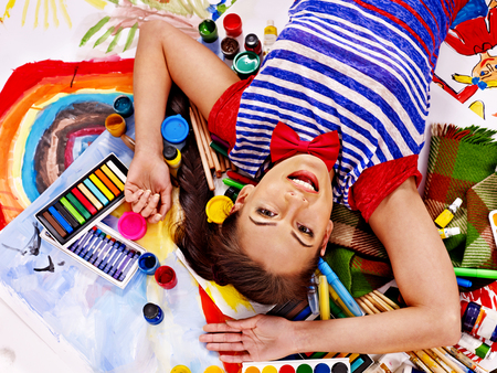 Artist woman lying on paint palette. photo