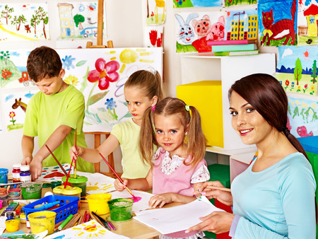 Happy children  with teacher painting. photo