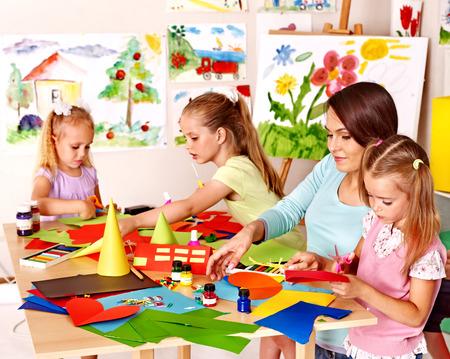 Children  cutting out scissors paper in preschool.