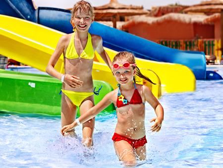 bikini wear: Children on water slide at aquapark. Summer holiday. Stock Photo