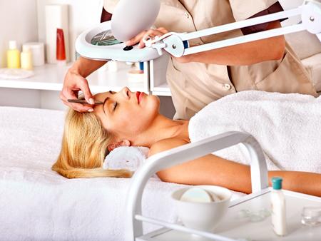 tweezing: Woman getting tweezing eyebrow. Stock Photo