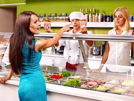 cafeteria tray: Women at cafeteria buying food.