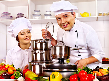Happy man in chef hat and woman cooking at kitchen. Stock Photo - 27461814