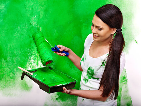 Happy woman paint wall at home. Stock Photo - 27461860