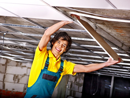 millwright: Man in builder uniform installing suspended ceiling