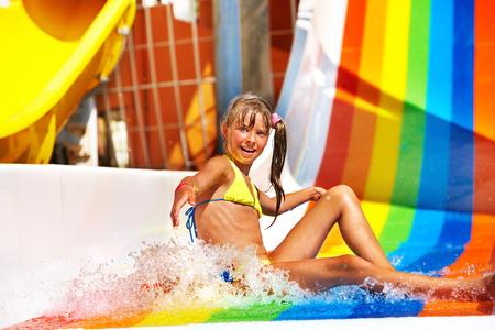 bikini wear: Happy child girl in yellow bikini sliding water park.