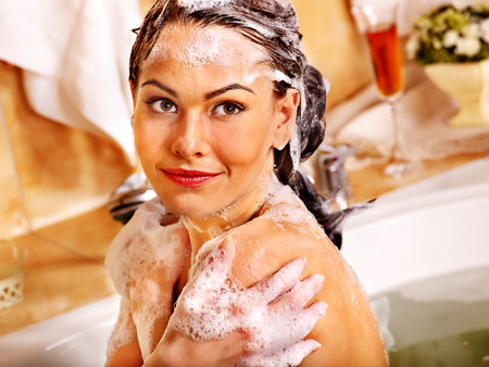 Happy woman washing hair in bubble bath. photo