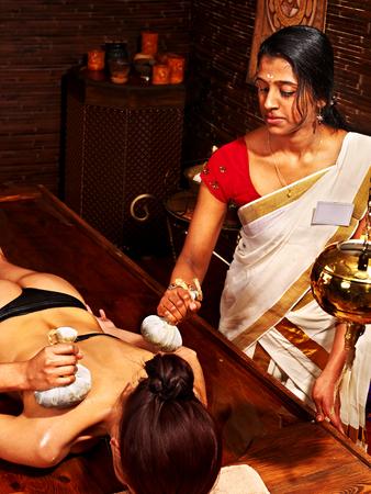 panchakarma: Woman having Ayurveda massage with pouch of rice.