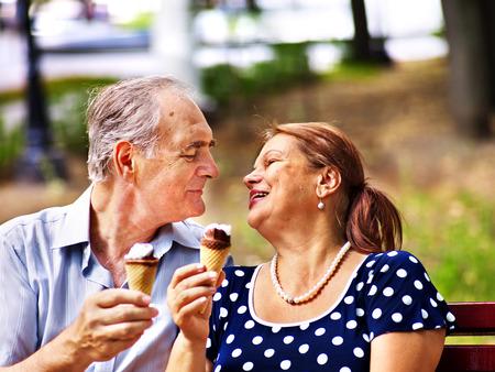 Happy old couple eating ice-cream outdoor. Stock Photo