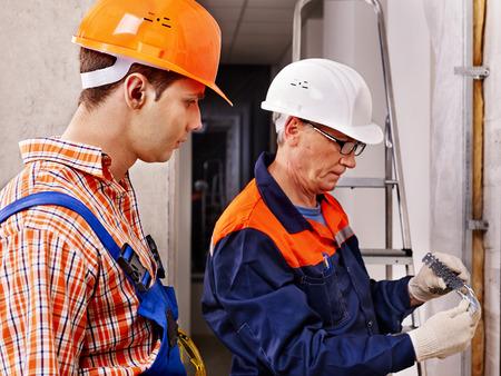 Happy group people men in builder uniform indoor  Standard-Bild