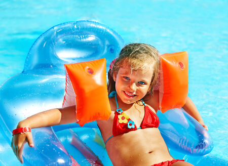armbands: Little girl swimming on inflatable beach mattress. Stock Photo