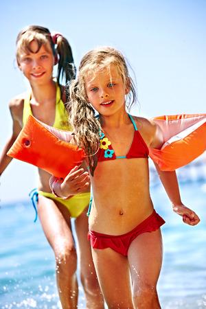 armbands: Little girl  running on  beach.