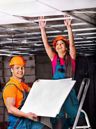 People in builder uniform installing suspended ceiling photo