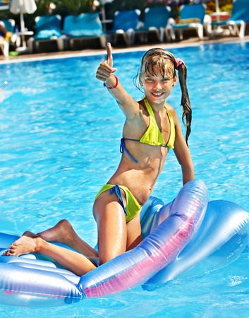 Little girl swimming on inflatable beach mattress. photo