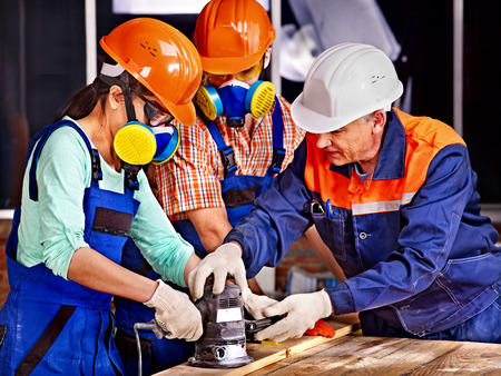 planer: Man and woman in builder helmet with electric planer. Stock Photo