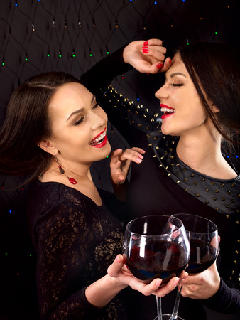 Two sexy lesbian women with red wine.Black background. photo