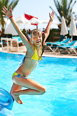 Little girl  jump in swimming  pool. photo