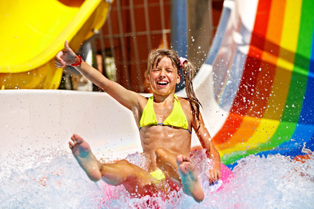 Happy child girl in bikini sliding water park. photo