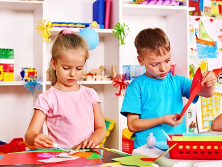 play blocks: Child boy cutting out scissors paper in preschool.