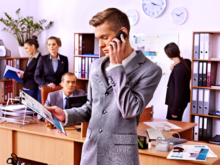 Businessman calling by mobile phone in office. photo