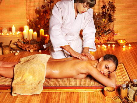 Therapist man giving Thai stretching massage to woman. Stock Photo