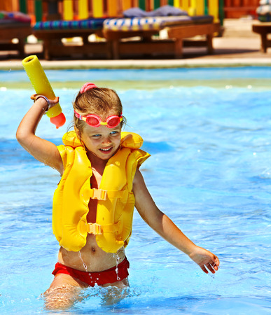 Happy child playing in swimming pool. photo