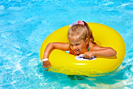 float tube: Child  on inflatable ring in swimming pool.