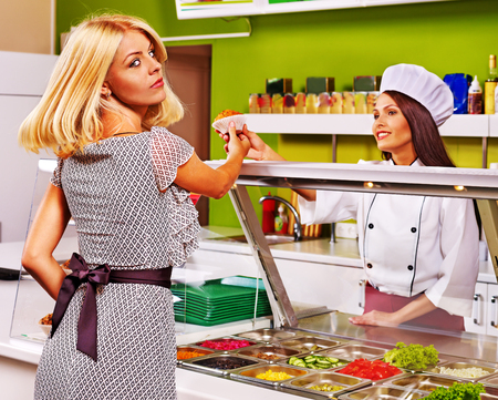 cafeteria tray: Young woman at cafeteria buying food. Stock Photo