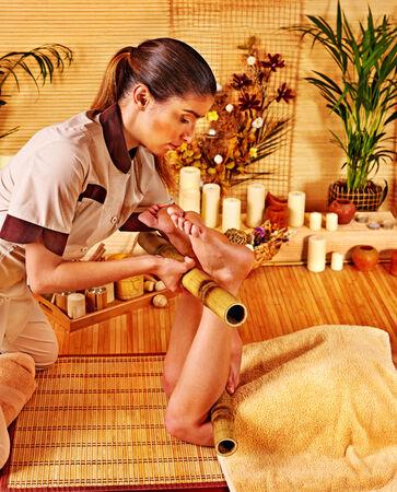 Young woman getting bamboo massage. Male therapist. photo