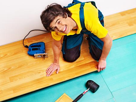 laminate flooring: Happy men laying parquet at home.
