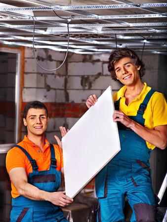 Men in builder uniform installing suspended ceiling photo