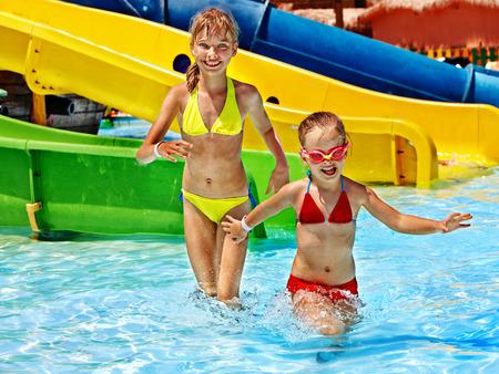Children on water slide at aquapark. Summer holiday. Stock Photo