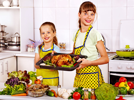 Happy children  cooking chicken at kitchen  photo