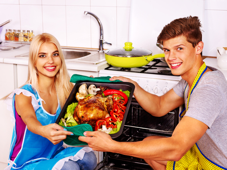 Happy couple cooking chicken at kitchen. photo