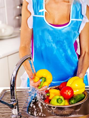 Happy woman washing fruit at kitchen. photo