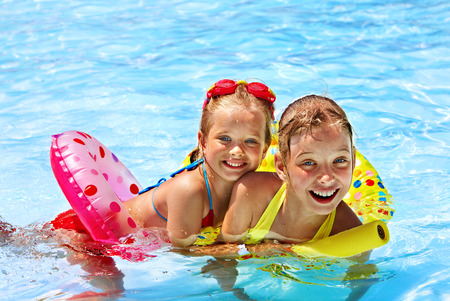 kids playing water: Children sitting on inflatable ring in swimming pool. Stock Photo
