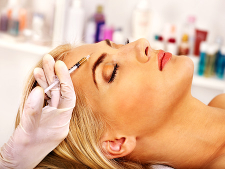Beauty woman giving botox injections. Stock Photo