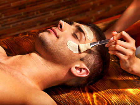 body mask: Man with clay facial mask in beauty spa.