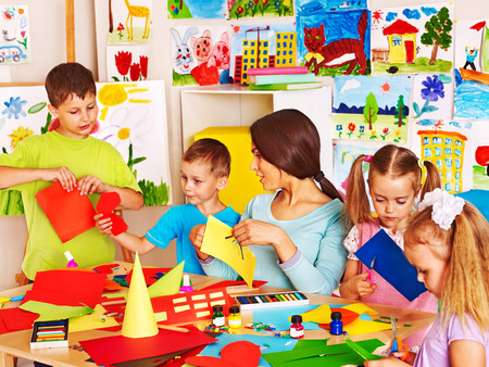 Happy children  with scissors at classroom. Standard-Bild