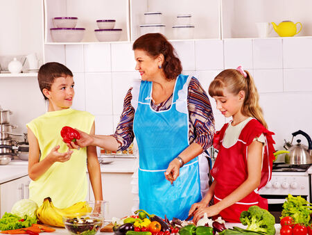 Family with grandmother and child cooking at kitchen. photo