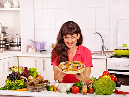 Happy woman cooking pizza at home kitchen. photo