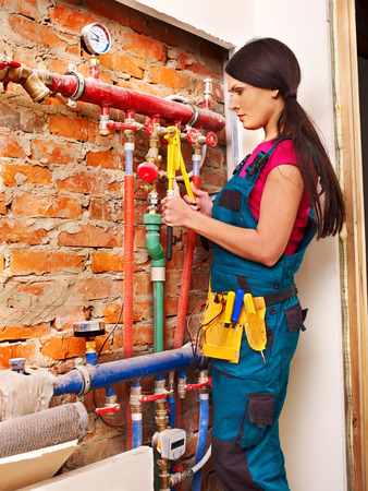 heat pump: Woman  builder fixing heating system with special tool.