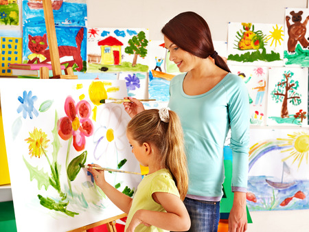 Glückliche Kinder, die mit Lehrer malen.