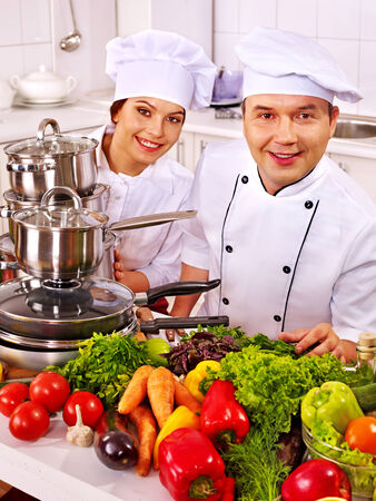 family kitchen: Happy man in chef hat cooking chicken. Stock Photo