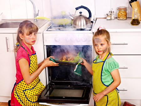 Kinderen met verbrande kip koken in de keuken.