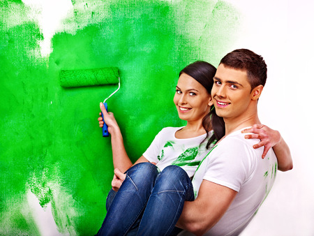 painting and decorating: Happy family paint wall at home.