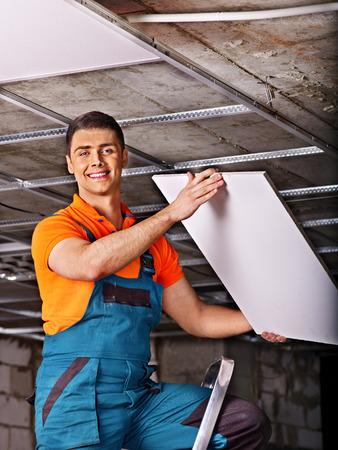 Man in builder uniform installing suspended ceiling photo